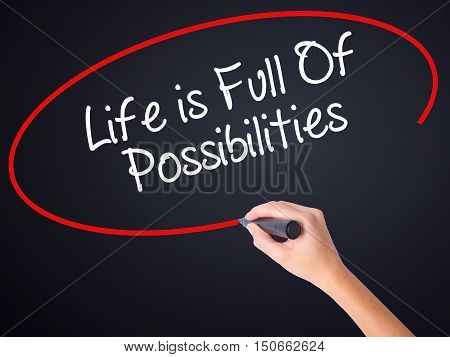 Woman Hand Writing Life Is Full Of Possibilities With A Marker Over Transparent Board