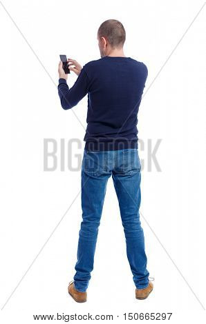 back view of man in suit  talking on mobile phone.    rear view people collection. Isolated over white background. backside view of person. Man in black warm sweater holding a phone.
