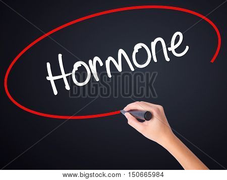 Woman Hand Writing Hormone With A Marker Over Transparent Board
