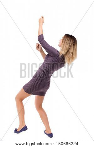 back view of standing girl pulling a rope from the top or cling to something. girl  watching. Rear view people collection.  backside view of person.  Isolated over white background. Girl in dress from