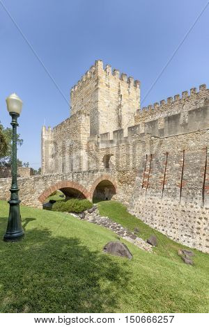 Walls, tower and bridge across the moat of Saint George Castle at Lisbon