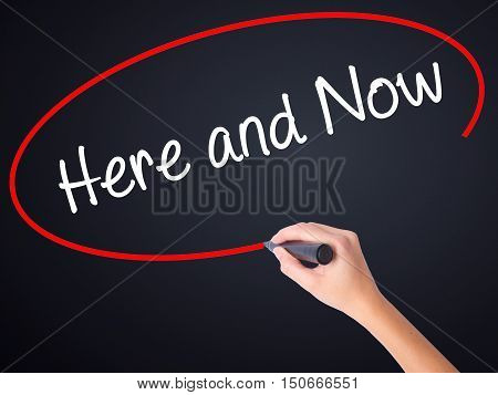 Woman Hand Writing Here And Now With A Marker Over Transparent Board