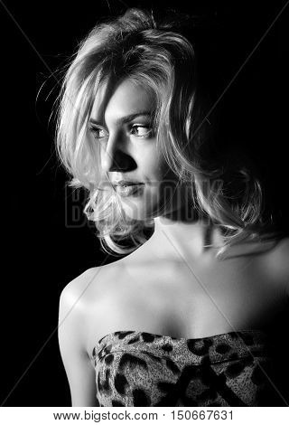 Portrait of a young blond woman with beautiful curling hair and professional make-up. black and white on a dark background.
