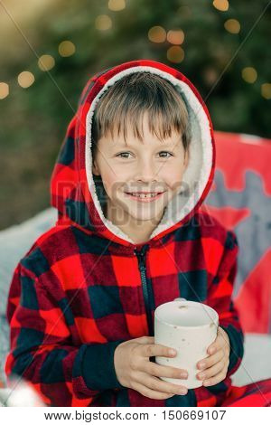 in the woods on the bed sits a boy in a red suit with a cup