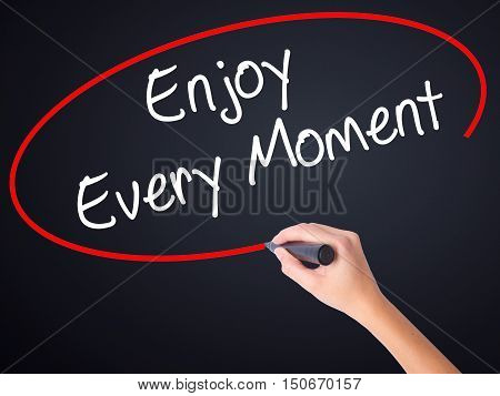 Woman Hand Writing Enjoy Every Moment With A Marker Over Transparent Board .