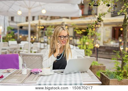 Happy business woman working on laptop and talking on the phone