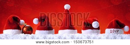 Seven red santa hats isolated on red background.Christmas red background with Santa hats.Happy new year 2017 santa hats.