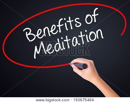 Woman Hand Writing Benefits Of Meditation With A Marker Over Transparent Board .