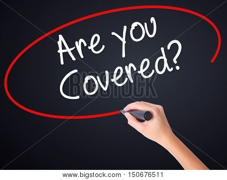Woman Hand Writing Are You Covered? With A Marker Over Transparent Board