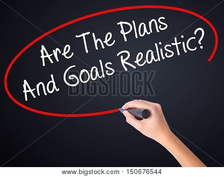 Woman Hand Writing Are The Plans And Goals Realistic? With A Marker Over Transparent Board .