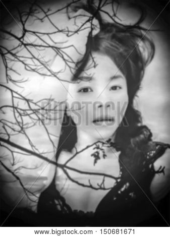 de-focused Beautiful sexy woman in black lace lingerie with double exposure of sunset scene and silhouette of tree black vignette in antique black and white tone