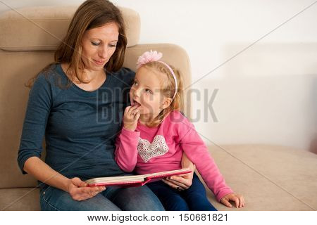 mother reads a book to her daughter in living room