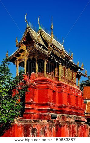 Lamphun Thailand - December 28 2012: Library repository built upon a red sandstone base with gilded roof and chofah ornaments at Wat Phra That Haripunchai Maha Viham *