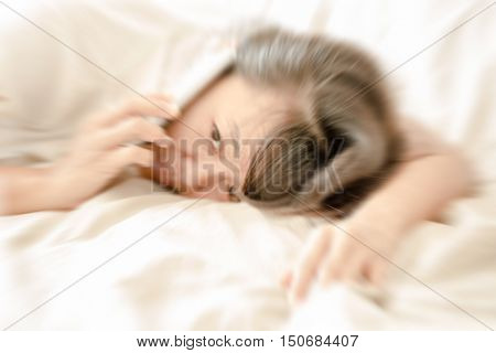 de-focused and zoom blur Woman lying on white bed wake up to chats on a mobile phone while sleepy emotion close up profile view