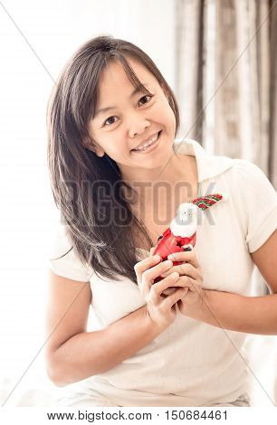 close up smile asian woman in white clothes holding toy of Santa in hand vintage tone