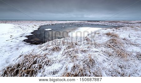 Typical Icelandic dramatic landscape with frozen lake near the Atlantic ocean in Iceland