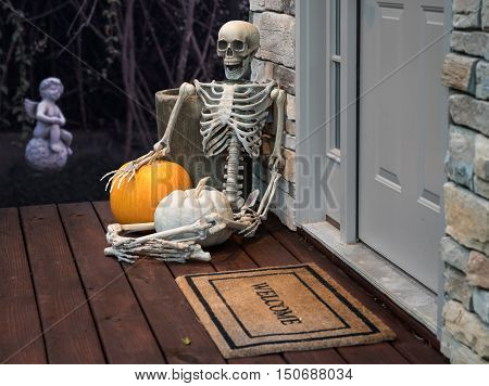 Scary skeleton sitting on porch of modern house by front door with welcome mat and garden in background. Funny Halloween image for trick or treat