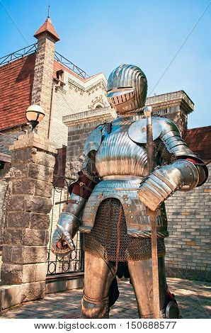 Medieval knight in chain armor with a sword with lowered visor helmet protects the ancient castle.