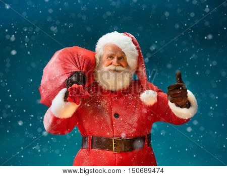 Happy Santa Claus gesturing thumb up with big bag full of gifts to children. Merry Christmas & New Year's Eve concept.