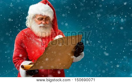 Kind Santa Claus reading vintage paper with wishes. Merry Christmas & New Year's Eve concept.