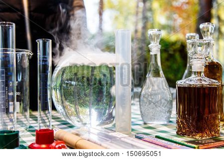 The Forest Alchemists. Some Flasks And Test Tubes With Gurgling Water In The Background Of The Fores