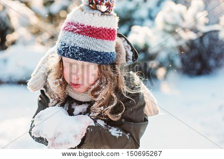 child girl playing with snow in winter garden or forest making snowballs and blowing snowflakes. Seasonal outdoor activities for kids