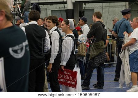Manheim PA - October 1 2016: An Amish woman holds Donald Trump campaign signs at a political rally.