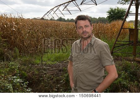 Happy farmer in the field checking corn plants during a sunny summer day agriculture and food production concept