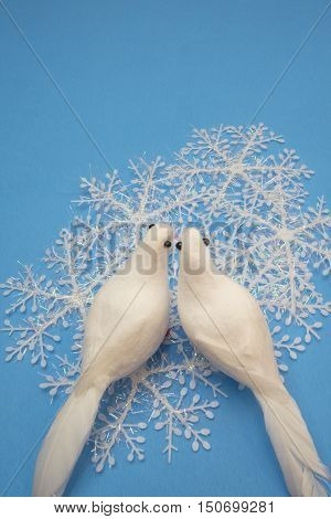 Two white doves with snowflakes on a blue surface