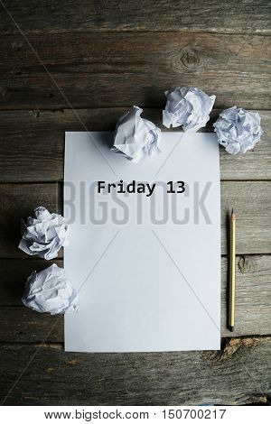 Crumpled up papers with a sheet of blank paper and a pencil on grey wooden background, friday 13