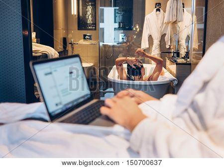 Couple in top level hotel: man working using laptopfemale bathing on the background