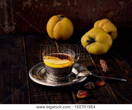 tea with quince, sugar, three of quince, a teaspoon on the wooden background