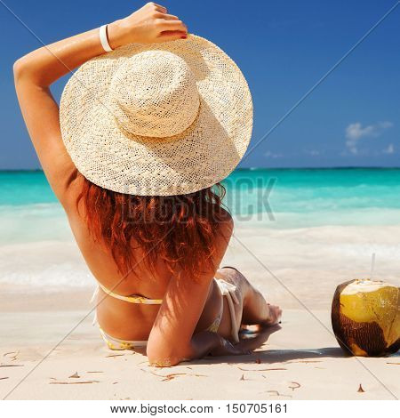 Young fashion woman relax on the beach. Happy island lifestyle. White sand, blue cloudy sky and crystal sea of tropical beach. Vacation at Paradise. Ocean beach relax, travel to desert islands