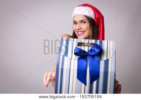 Young latina woman holding some christmas gift