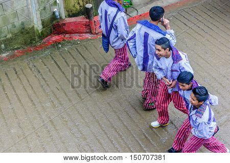 Todos Santos Cuchumatan, Guatemala - November 1 2011: Traditionally dressed local youths walk in street during All Saints' Day celebrations in highland town