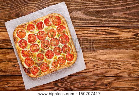 Tart with tomato and fresh herbs on a wooden table. Healthy eating Vegetable Pie top view.