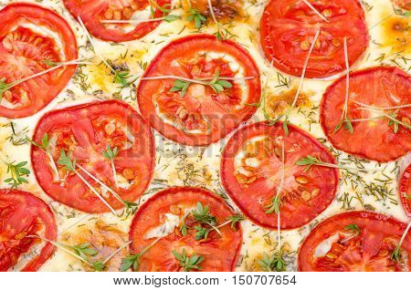 Tart with tomato and greens close-up food background