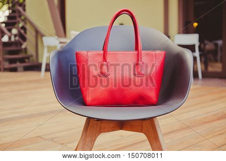 Fashion and trendy. Style large red handbag stands on a beautiful chair made of plastic in a summer cafe in the evening.