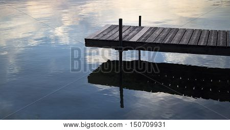 Dock on a lake with clouds reflected in water