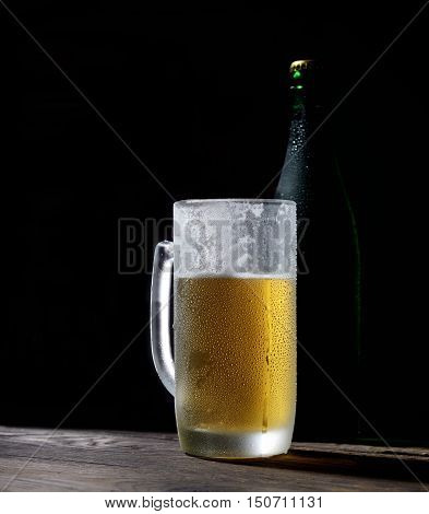 cold frothy beer in a glass and bottle on wooden boards on a black background
