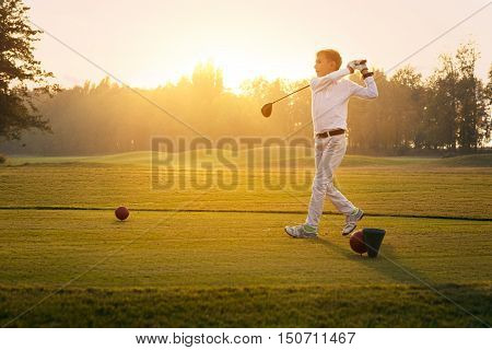 Boy golf player hitting by iron from fairway at sunset