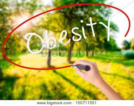 Woman Hand Writing Obesity With A Marker Over Transparent Board