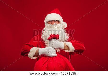 christmas santa claus with big bag on shoulder glasses on red background