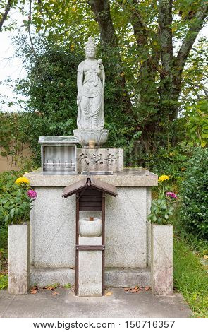 Kyoto Japan - September 15 2016: At the Shinnyo-do Buddhist Temple the statue of Kwan Yin the most important female in Buddhism stands in the garden. She is the avatar of bodhisattva Avolikiteshvara.