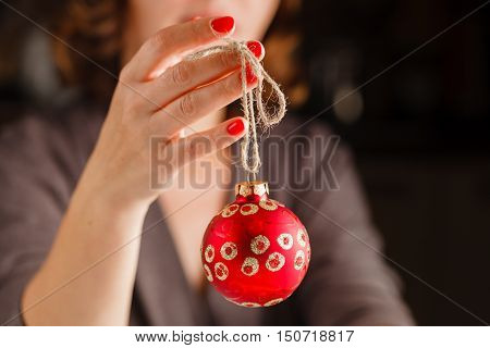 Girl Holding Christmas Ball In Fingers. Beautiful Manicure On A Background Of The Red Ball.
