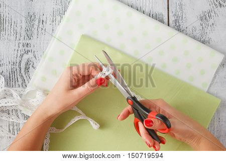 The Seamstress Cuts Out A Pattern On Fabric On A Table