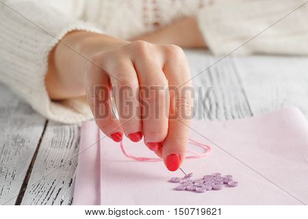hand hold needle sew a button on cloth