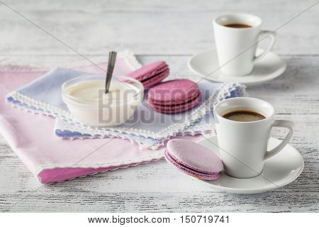 Frothy coffee on table with macaroons on napkin