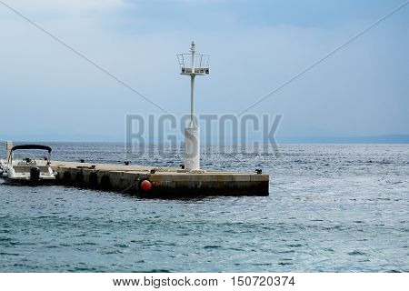 White lighthouse beacon tower on stone pier platform with motor boat at moorage on blue sea and sky