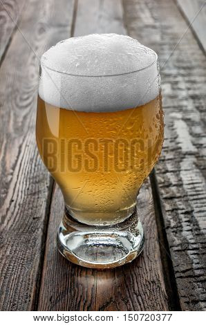 Glass beer on dark wood table. Close-up